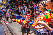 13 APRIL 2013 - BANGKOK, THAILAND:  Thais have a water fight during Songkran celebrations on Soi Nana, off of Sukhumvit Road in Bangkok. Songkran is celebrated in Thailand as the traditional New Year's Day from 13 to 16 April. The date of the festival was originally set by astrological calculation, but it is now fixed. If the days fall on a weekend, the missed days are taken on the weekdays immediately following. Songkran is in the hottest time of the year in Thailand, at the end of the dry season and provides an excuse for people to cool off in friendly water fights that take place throughout the country. Songkran has been a national holiday since 1940, when Thailand moved the first day of the year to January 1.   PHOTO BY JACK KURTZ