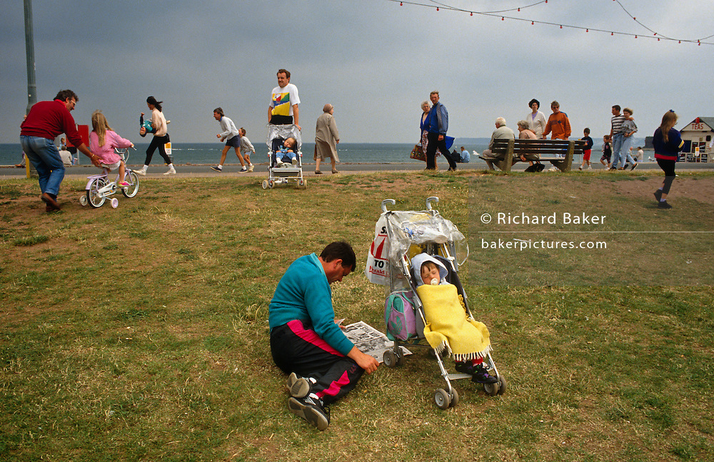 Three dads are looking their respective children of varying ages - from a baby to an infant and 8-year old. In the foreground a father reads his tabloid newspaper as his toddler sleeps contentedly in its pushchair, a dummy in the mouth and a blanket scross its body to keep out a chilly breeze. Further back another man stands waiting for his partner with a baby, also asleep in the buggy. And thirdly, a male pushes his daughter in pink up a small slope on a bicycle that uses stablizers. It is a busy scene on Paignton seafront on the Devon coast. Elsewhere children and adults of all ages walk along the esplanade enjoying an overcast and windy day on holiday. This theatrical scene is about the ideal father and the family unit.