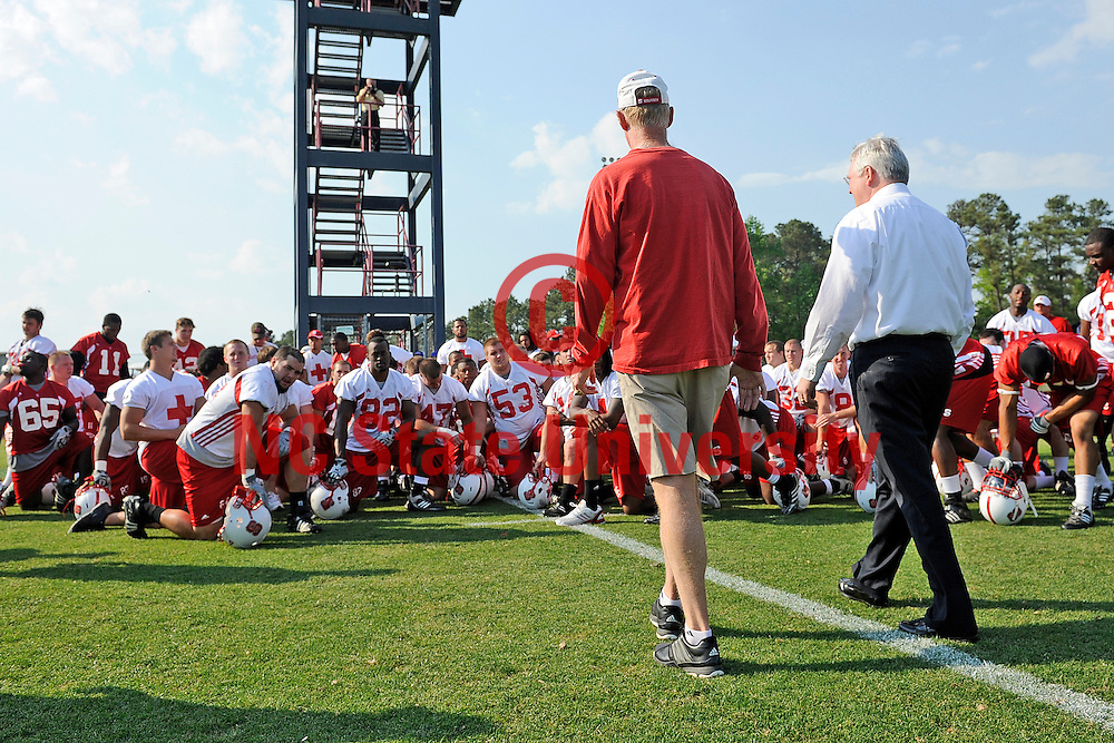 Chancellor Randy Woodson walks with football coach Tom O'Brien at football practice