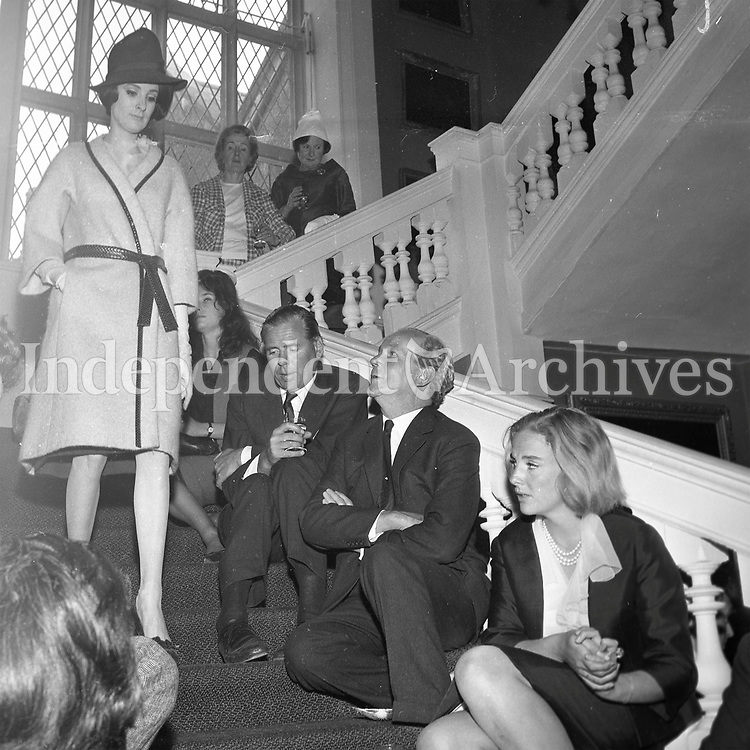 People sitting on stairs whilst lady in fashionable coat and hat descends. <br />