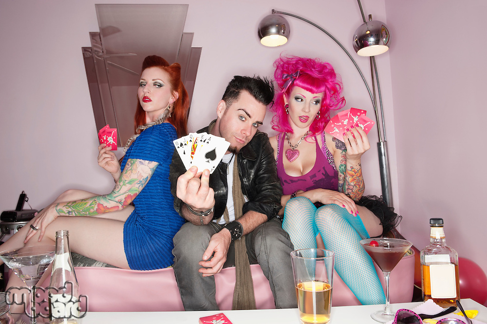 Man showing playing cards tattooed sexy women sitting besides