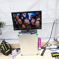 A broadcast showing the arrival of bishops within Westminster Abbey for the wedding of Prince William and Kate Middleton is displayed on the 3rd level of the media riser across the street from the ceremony.