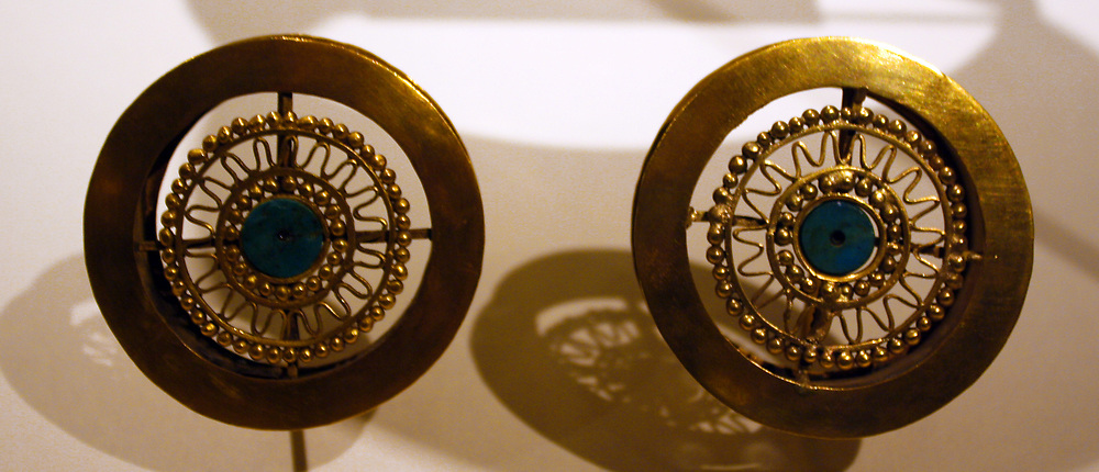 Pair of Earflares. Peru; Sican (Lambayeque) 9-11th century.  Hammered gold, turquoise inlay.  Archaeologists recently excavated a temple platform, where, almost forty feet below they found the tomb of a mighty Sican lord laid to rest with all the trappings of his power and wealth.