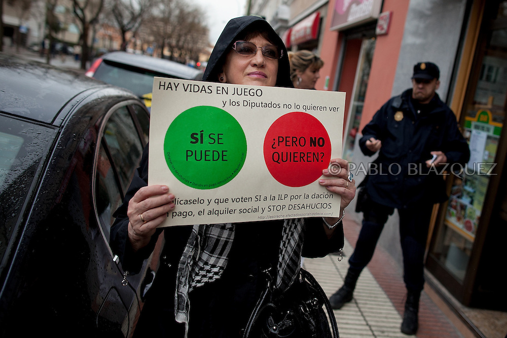 An anti-eviction activists holds a placard during a a 'escrache' outside the house of Popular Party Deputy Mari Luz Prieto while riot police secures the building entrance, on April 4, 2013 in Madrid, Spain. Placard reads 'Yes we can, but they don't want'. The Mortgage Holders Platform (PAH) and other anti evictions organizations are organizing 'escraches' for several weeks under the slogan 'There are lifes at risk' to claim the vote for a Popular Legislative Initiative (ILP) to stop evictions, regulate dation in payment and social rent outside Popular Party deputies' houses and offices..'Escraches' are form of peaceful public protest that was used in Argentine in 1995 to point to pardoned genocides of Argentenia's Dictatorship within their neighborhoods.