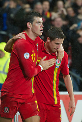 CARDIFF, WALES - Friday, October 12, 2012: Wales' Gareth Bale celebrates with Joe Allen after scoring the winning second goal against Scotland during the Brazil 2014 FIFA World Cup Qualifying Group A match at the Cardiff City Stadium. (Pic by David Rawcliffe/Propaganda)
