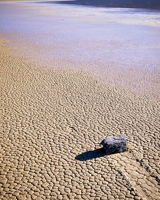 A 'running' rock at the racetrack playa west of Death Valley National Park. The water is actually ice. The stone, although showing evidence of motion, is frozen in its track. This phenomenon is still unexplained; scientists disagree on how or when the rocks move, but they do move, leaving trails in the mud. The image of the stone seems to pose man's greatest questions in life: 'Where did I come from? Why am I here? Where am I going?""