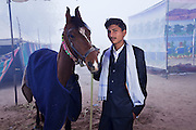 Khoju Ram (19yrs) is the son of Bhanwar Singh (33)and lives in Nagaur. He is staying at the fair with his family. He is photographed with Suman (4yrs) from Kathiawad who will sell for 3.5 lakhs. He is the 4th generation to look after horses. Brother - Raju Ram's # 09829626389<br /> Nagaur Cattle Fair In Rajasthan takes place annually in January. It only has male calves (bachra) and bulls (bel), no cows. There are, however, female horses and camels allowed. People come from all over North India to buy and sell cattle. Some people come to 'dance' their horses and camels.<br /> I met Mahendra Singh from Haridwar, Uttarakhand who took me around the fair and helped me by telling everyone I am Indian, so they would not hassle me. 09012837793 & 09058793325<br /> The organiser of the fair is Dr. G.L. Lunia - 09414664900 ddahnagaur@yahoo.co.in