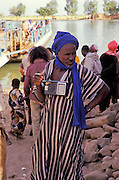 Timbuctou, Mali, West Africa - Elderly Taureg  man listens to old portable radio hanging around his neck while waiting for the ferry to cross the Niger river.