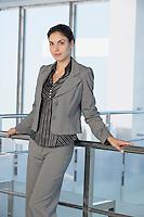 Business woman against railing in office building portrait