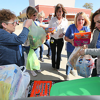 Lucy Nash, from left, Emily Jarrett, Susan Meredith, Debbie Banko, Lauren Hurt and Mika Brown start unloading bags and boxes full of food that will be used to fill up the Tupelo High School food pantry.