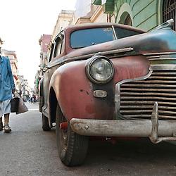 Old woman walking by a vintage car. Ciudad de La Habana, Cuba, Caribbean.