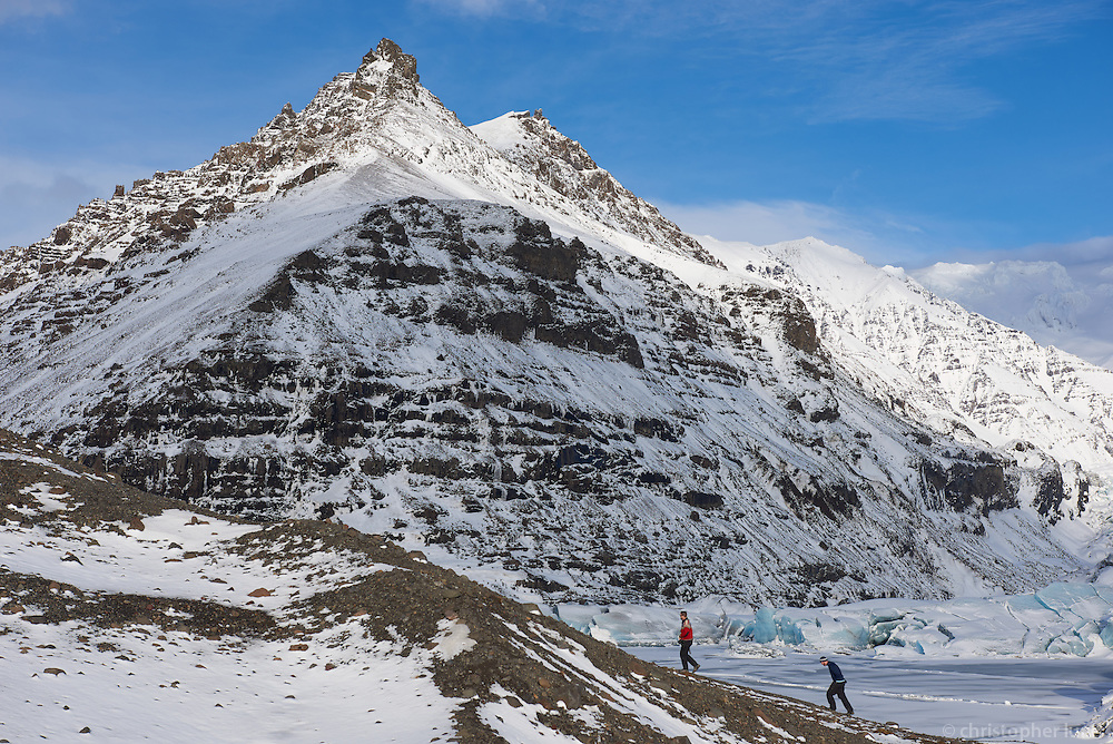 Hikers by Svínafellsjökull outlet glacier in winter, Southeast Iceland.