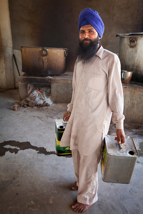 A cook carries oil in a Sikh kitchen. the workforce of Sikh kitchens is mostly made of volunteers.