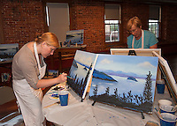 Beth San Soucie and Susan Finn work on their paintings during the Wine and Design event at the Belknap Mill Tuesday evening.  (Karen Bobotas/for the Laconia Daily Sun)