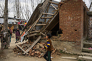 Shugufta's house which was destroyed by floods in Narbal village, Jammu and Kashmir, India, on 24th March 2015. When the floods hit in the middle of the night, Shugufta and her family had to walk 5 miles to find shelter. Save the Children supported the family with shelter kits, blankets, hygiene items, food and tarpaulin, which they have used to build a temporary shelter next to their crumbled home. Photo by Suzanne Lee for Save the Children