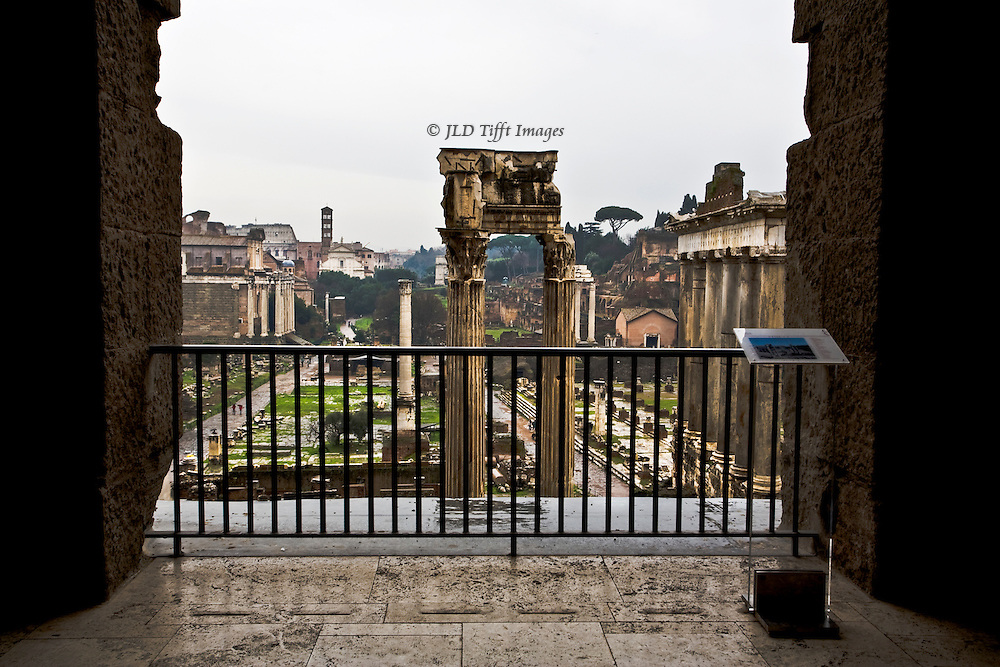 Overview of the Roman forum from the overlook at the back of the Capitoline Museum, looking through an arched opening and over a protective barrier.