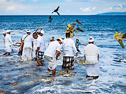 20 JULY 2016 - KUSAMBA, BALI, INDONESIA:   Balinese Hindu community leaders throw an offering into the ocean after a prayer service. Several hundred Balinese Hindus gathered on the beach in Kusamba, Bali, for a ceremony to honor the full moon. They prayed for more than hour and then community leaders threw an offering into the ocean.      PHOTO BY JACK KURTZ