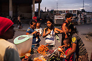 Cemetery inhabitants buy street food and go about their daily lives in an inhabited cemetery in Paranaque City, Metro Manila, The Philippines on 18 January 2013. Photo by Suzanne Lee for Save the Children UK
