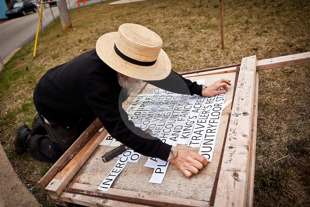 Amish man works on a sign during the Annual Mud Sale to support the Fire Department in Gordonville, PA.