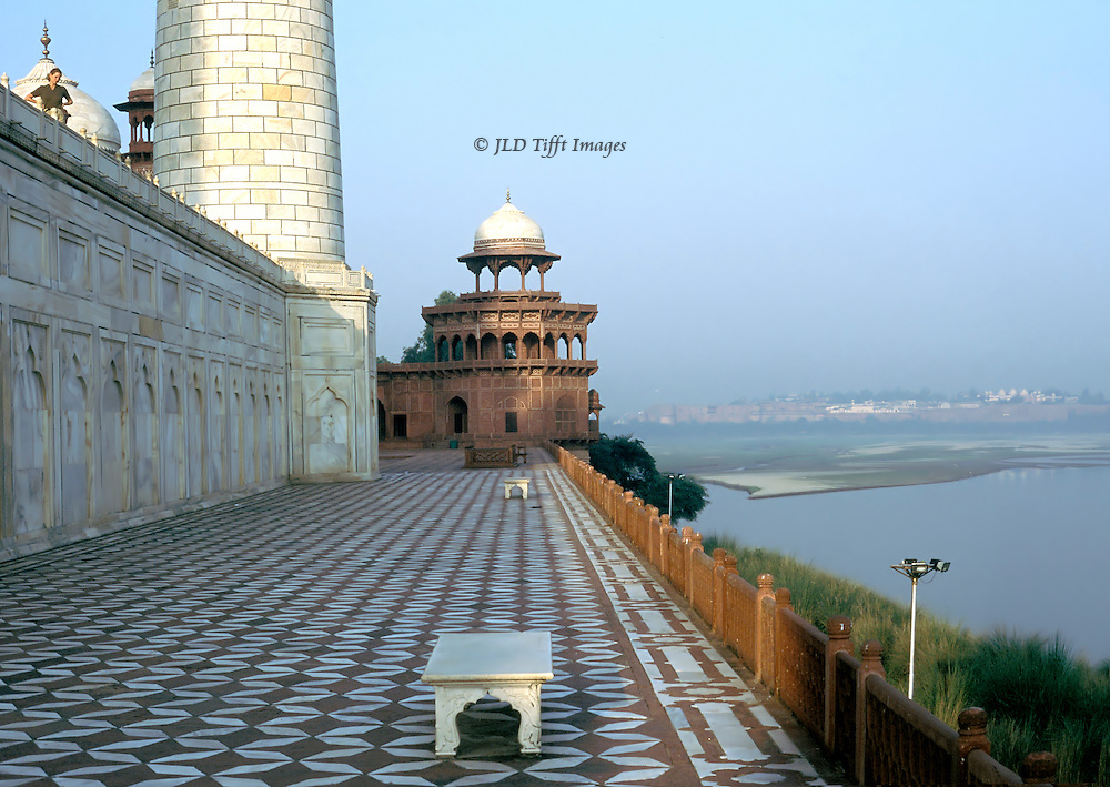 Taj Mahal terrace, looking westward along the Jumna River. Part of the adjoining mosque and its chhatri.  Bench for visitors to enjoy the view, empty now.