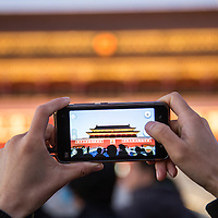 China, Beijing, Visitor takes snapshots with cellphone camera outside Gate of Heavenly Peace at Forbidden City by Tiananmen Square at dusk