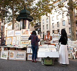Artist Pascale Cozic welcomes two tourists to her art stand in the Place de L'Horloge in Avignon, France.