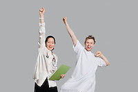 Portrait of doctor and patient cheering up with raised arms