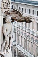 Milan, Italy, Duomo Cathedral. Statue of a man next to a stone dragon gargoyle on the side of the building.