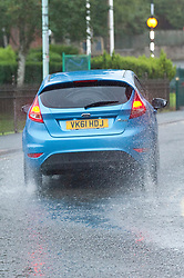 © Licensed to London News Pictures. 14/08/2019. Builth Wells, Powys, UK. A car drives through surface water in Builth Wells in Powys after heavy rain last night. Photo credit: Graham M. Lawrence/LNP