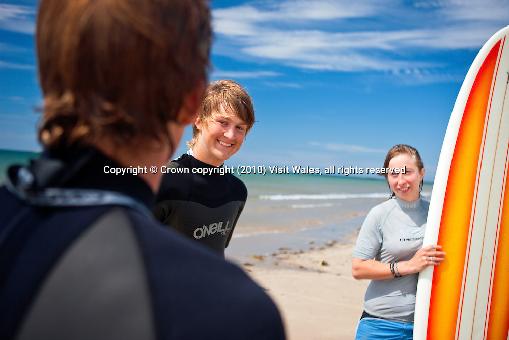 Three friends chatting on beach<br /> Surfing<br /> Rhosneigr<br /> Anglesey<br /> North<br /> Activities And Sports