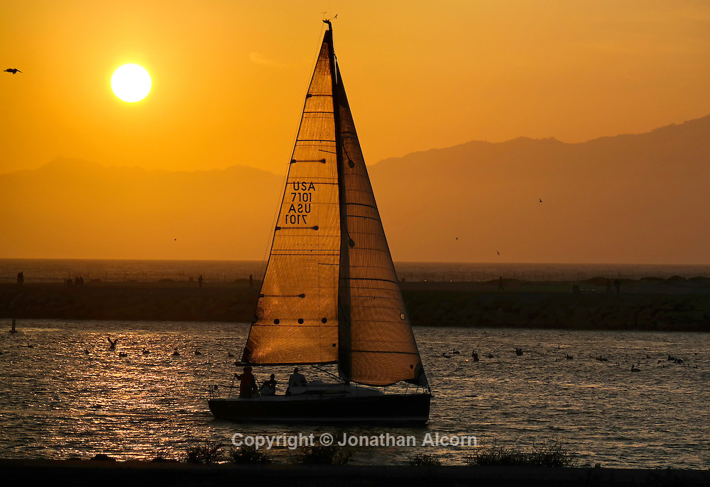 A sailboat returns to Marina del Rey as the sun sets over Malibu and the Santa Monica Mountains in the distance.