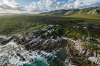Aerial view of an Isolated farmstead along the coastline with green mountains in the background and an overcast sky, Agulhas National Park, Western Cape, South Africa
