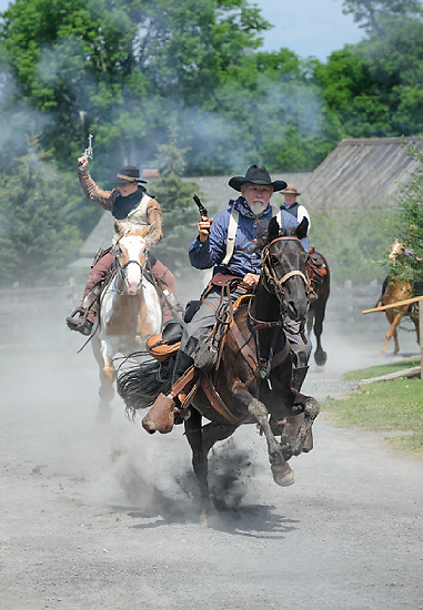 Cowboys riding horses hard and fast through town shooting blazing six guns, rowdy men making trouble with lots of dust and action.