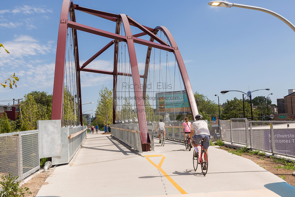 Bicyclists at the Milwaukee Avenue bridge on the 606 elevated bike trail, green space and park built on the old Bloomingdale Line in the Logan Square neighborhood of Chicago, Illinois, USA