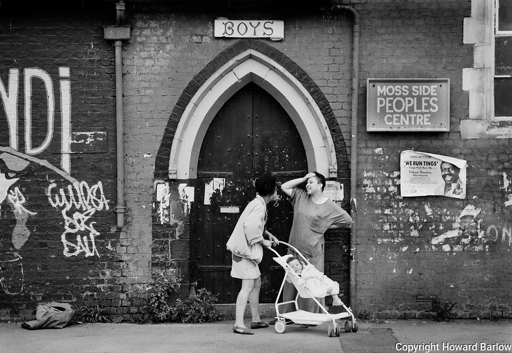 Moss Side People&rsquo;s Centre &ndash; 1991<br /> Young mums chat outside the Boys entrance, with Oliver Samuels &lsquo;We run tings&rsquo;<br /> poster hanging off the wall publicising the Blue Mountain Theatre&rsquo;s Manchester Palace show.