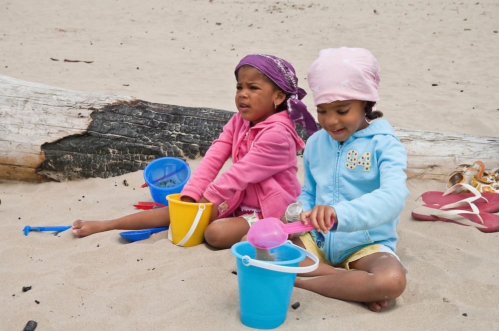 Two little girls playing in the sand on Cannon Beach, Oregon Coast.