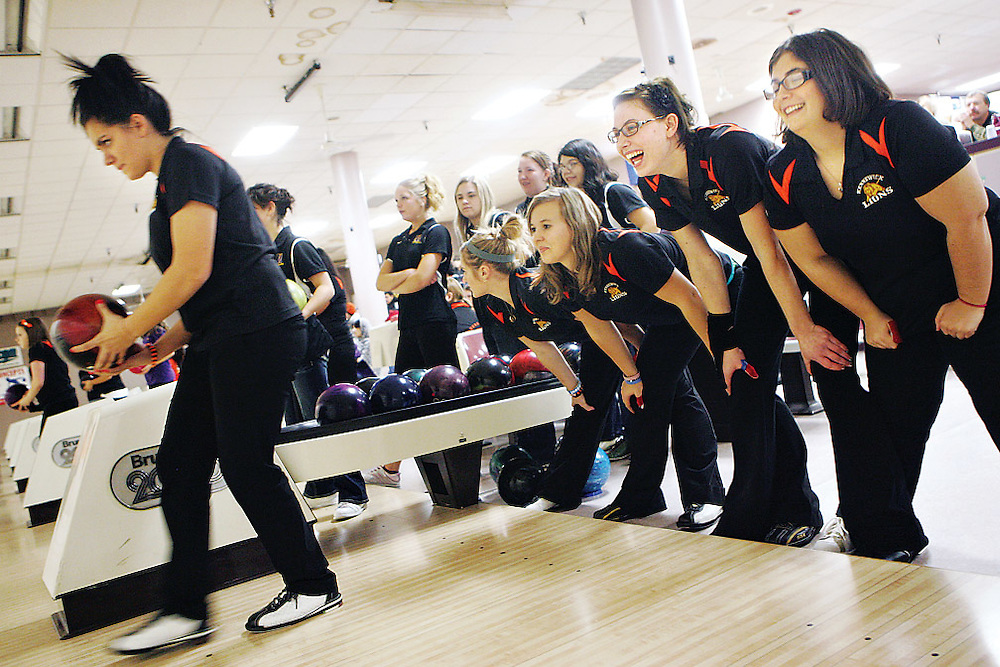 """Ashlen Ayers, 17, prepares to bowl in a baker during a match against Wenatchee at home while teammates Charlotte Johnson, 17, right, Dayna Bolt, 17, Karissa Shiflet, 16, and Brittany Blackketter, 17, show their support with a """"power stance"""" that Ashlen's dad Lenny passed along to Ashlen from his baseball and football days. During the baker rounds, the team rotates through each bowler frame by frame."""