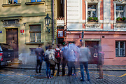"Visitors are waiting to enter Prague's narrowest street which has a traffic light for pedestrians and leads to a restaurant located at ""Certovka"" (Devil's Canal"" at Lesser Town"" (Mala Strana)."