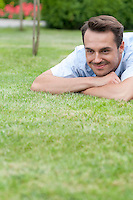 Happy young man lying on grass in park