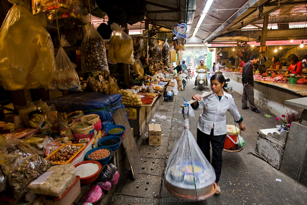 A street vendor carries her merchandise at Cho Chau Long Market in Hanoi, Vietnam.
