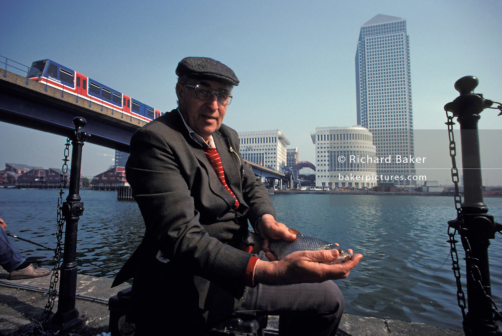 With the background of new office development at London Docklands that will in later years will change considerably, a portrait of a local middle-aged fisherman holding a fish that he has caught in the old 19th century dock waters at Canary Wharf, on 18th May 1991, in London, England.