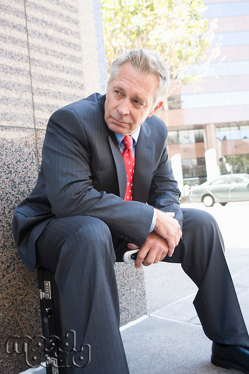 Middle-aged businessman relaxing outdoors