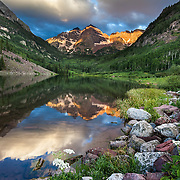 The still waters of Maroon Lake reflect Maroon Peak and North Maroon Peak (called the Maroon Bells) at sunrise in summer near Aspen, Colorado.