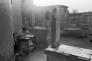 Cairo, Egypt, The City of the Dead, 2000 - high school student does her school work at her desk set up between the grave markers.