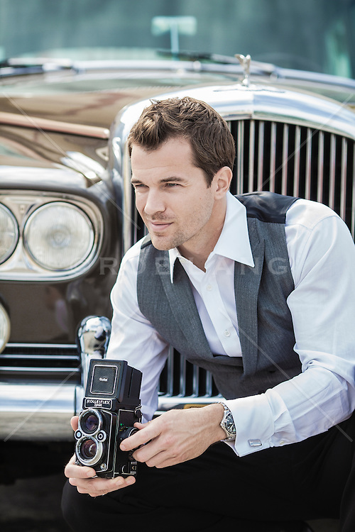 man with a vintage twin lens reflex camera outdoors by a car
