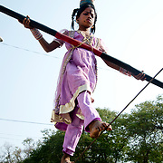 India. Bihar. Bodhgaya, the town where the Buddha sat under a sacred fig tree (bhodi tree) and received enlightenment. A young girl performs on a tightrope in order to get tips from passers-by.