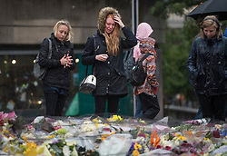 © Licensed to London News Pictures. 06/06/2017. London, UK.  Nicola Smith (centre) the ex-girlfriend of attack victim James McMullan, is comforted by her sister as they stand over flowers at London Bridge, left for those who lost their life in a terrorist attack on Saturday evening. Three men attacked members of the public  after a white van rammed pedestrians on London Bridge.   Ten people including the three suspected attackers were killed and 48 injured in the attack. Photo credit: Ben Cawthra/LNP