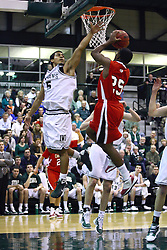 29 January 2011: Eliud Gonzalez attempts to block a shot by Malcom Kelly during an NCAA basketball game between the Carthage Reds and the Illinois Wesleyan Titans at Shirk Center in Bloomington Illinois.