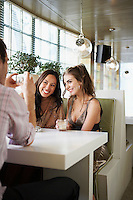 Man Photographing smiling Friends sitting side by side in cafe