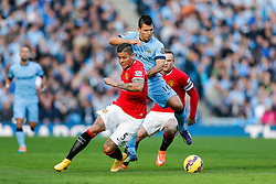 Sergio Aguero of Manchester City is challenged by Marcos Rojo and Wayne Rooney of Manchester United - Photo mandatory by-line: Rogan Thomson/JMP - 07966 386802 - 02/11/2014 - SPORT - FOOTBALL - Manchester, England - Etihad Stadium - Manchester City v Manchester United - Barclays Premier League.